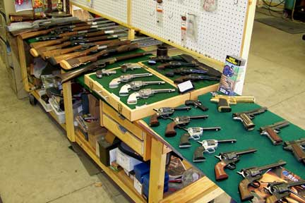 Work area showing some of the guns they work on or have for sale.